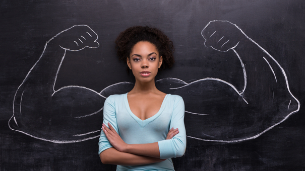 Serious afro-american woman with painted muscular arms on chalkboard